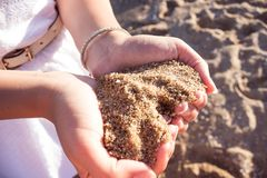 Mellow heart shaping female hands above beach. Hands of a young girl with a handful of seashells and sand in the form of a heart in the soft sunset sun on the stock photo