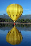Mellow Yellow. Hot air balloon taking a dip in the reflecting lake stock images