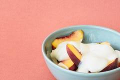 Melocotón en un cuenco con el yogur natural Fotografía de archivo libre de regalías