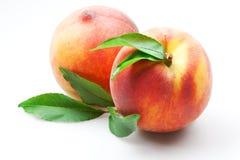 Melocotón. frutas con las hojas verdes aisladas en blanco Imagen de archivo libre de regalías