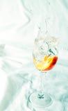 Melocotón y chapoteo del agua en un vidrio Fotos de archivo libres de regalías