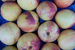 Melocotones frescos y jugosos en la parada azul del mercado para la venta Fotografía de archivo