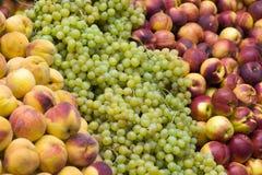 Melocotones y uvas en parada Fotografía de archivo