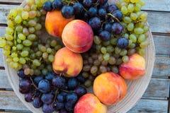 Melocotones y uvas en una placa en la tabla Imágenes de archivo libres de regalías