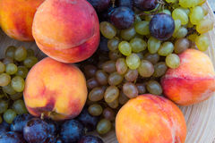 Melocotones y uvas en una placa en la tabla Foto de archivo
