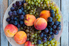 Melocotones y uvas en una placa en la tabla Fotografía de archivo