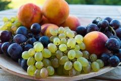 Melocotones y uvas en una placa en la tabla Fotos de archivo