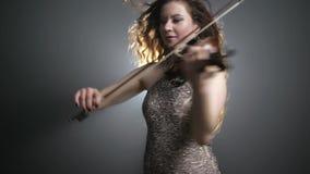 Melodía a solas, mujer en el vestido magnífico que juega en el instrumento atado en reflector brillante de la iluminación almacen de video