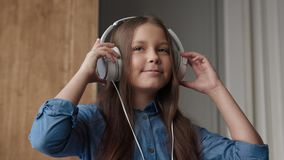 Happy child listening music or cute smiling girl with sound headphones. Melody play for carefree girl in domestic interior. Positive life and pleasure of listen