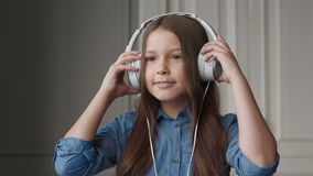 Happy child listening music or beautiful smiling girl with headphones. Melody playing for smiling carefree girl in room interior of house. Sweet people have
