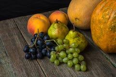 Meloen, druiven, perzik, Peer en pompoen op oude houten lijst Stock Afbeelding