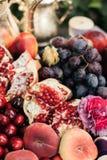 Melograno ed uva in un piatto sulla tavola di legno immagine stock libera da diritti