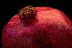 Melograno rosso maturo di grande su un primo piano nero del fondo fotografia stock