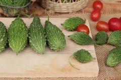 Melon amer et découpé en tranches sur le fond en bois Photos stock