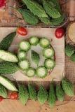 Melon amer et découpé en tranches sur le fond en bois Photos libres de droits