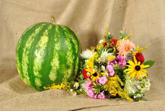 The melon and autumn flowers against rough stuff Stock Images