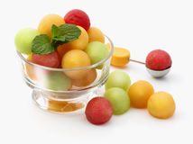 Melon Balls. In glass dish on white background with sprig of mint Royalty Free Stock Photos