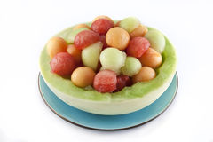 Melon balls in honeydew bowl. Half honeydew with watermelon, cantaloupe, and honeydew melon balls inside.  Image depicts healthful, refreshing snack or dessert Royalty Free Stock Images