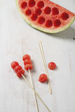 Melon balls on a stick with carved watermelon Stock Photos