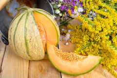 Melon with a bouquet of yellow flowers Royalty Free Stock Photo
