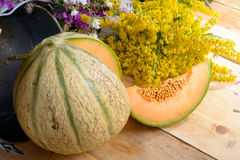 Melon with a bouquet of yellow flowers Stock Photos
