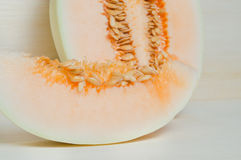 Melon or cantaloupe sliced on wooden board with seeds  Royalty Free Stock Photo