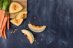 Melon and carrots on cutting board stock images