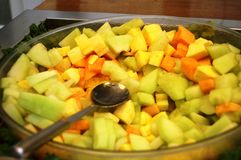 Melon Cubes. Large bowl of green and orange melon bites with spoon inserted Stock Photos