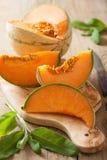 Melon de cantaloup coupé en tranches sur le fond en bois Photo libre de droits