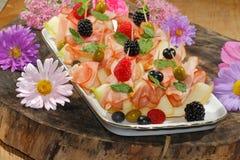 Melon de Galia, melon avec du jambon, framboises, myrtilles, blackberr Photographie stock