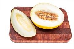 Melon de miellée sur la planche à découper d'isolement au-dessus du fond blanc Photographie stock libre de droits