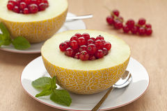 Melon filled with red currants Royalty Free Stock Photography