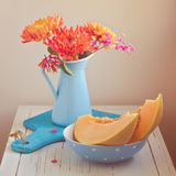 Melon and flowers on vintage table. Focus on melon. Retro filter effect Royalty Free Stock Photo