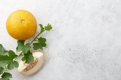 Melon frais de yelllow et vigne fleurissante sur le fond en pierre blanc Photo libre de droits