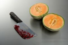 Melon fruit killed by a knife. Metaphor of a bloody knife after killing a melon fruit royalty free stock photo