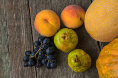 Melon, grapes, peach, Pear and pumpkin on old wooden table. Royalty Free Stock Image