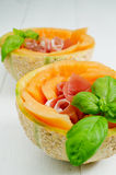 Melon with ham prosciutoo. Ham Prosciutto with melon and basil Royalty Free Stock Images