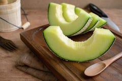 Melon juteux de tranche sur une table en bois image libre de droits