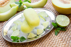 Melon and lime sorbet ice cream popsicles. Melon and lime sorbet ice cream on silver plate with ice cubes, lime pieces, mint leaves near melon slices, lime on a Stock Photography