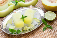 Melon and lime sorbet ice cream popsicles. Melon and lime sorbet ice cream on silver plate with ice cubes, lime pieces, mint leaves near melon slices, lime on a Stock Image