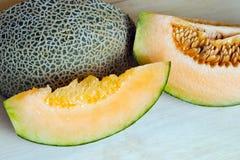 Melon lub kantalup pokrajać na drewnianej desce z ziarnami & x28; Także wezwanie zdjęcie royalty free