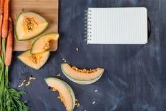 Melon och morötter på skärbräda Royaltyfri Foto