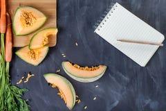 Melon och morötter på skärbräda med anteckningsboken Royaltyfria Foton