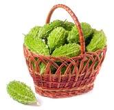 Melon ou momordica amer dans un panier en osier d'isolement sur le fond blanc Photo stock