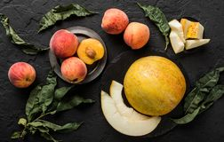 Melon and peaches. Creative layout made of fruits. Colorful fresh fruit on black stone background. Top view. Flat lay stock images