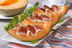 Melon with prosciutto and basil close-up horizontal Royalty Free Stock Photography