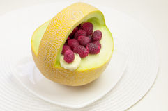 Melon with raspberries Royalty Free Stock Images