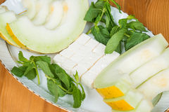 Melon slices with feta cheese and mint. On a wooden surface Stock Photo