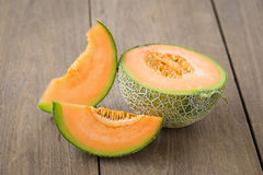 Melon with slices and on a wooden table Stock Image