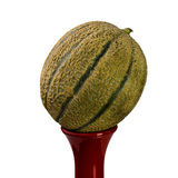 Melon on a Bottle. Melon standing on a red bottle. Studio isolated on white Royalty Free Stock Images